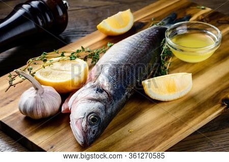 Fresh Fish Seabass. Raw Fish Seabass With And Herbs Ingredients For Cooking Raw Fish On A Cutting Bo
