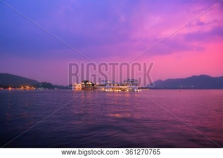 Romantic luxury India travel tourism - Lake Palace (Jag Niwas) complex on Lake Pichola on sunset in twilight with dramatic sky, Udaipur, Rajasthan, India