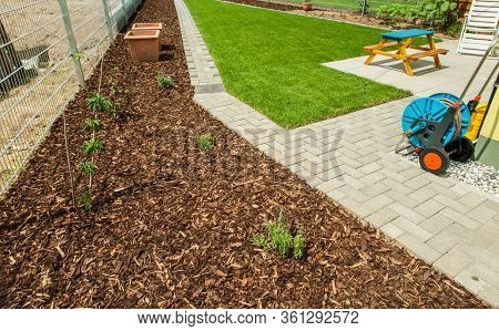Gardening - Garden with fresh new lawn and bark mulch area to reduce weed growth