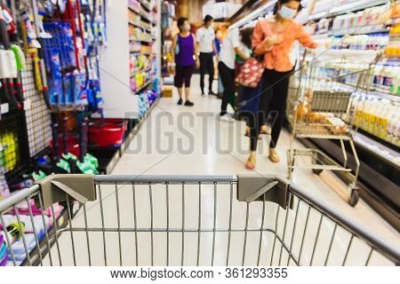 Shopping Cart With Blurred People In Face Mask In Super Market Covid-19 Social Distancing.