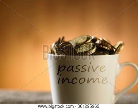 Saved Money in a mug to Finance Goals overflowing with  coins, passive income