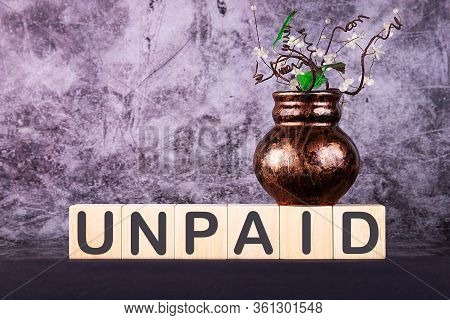 Word Unpaid Made With Wood Building Blocks On A Gray Background