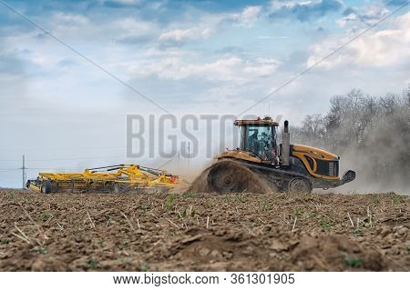 The Tractor On The Huge Field, A Farmer Riding A Tractor, A Tractor Working In A Field Agricultural
