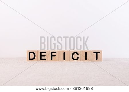 Deficit Word Concept Written On Wooden Cubes Blocks Lying On A Light Table And Light Background
