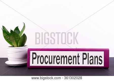 Ring Binder With Inscription Procurement Plans On A Black Table And On A White Background.