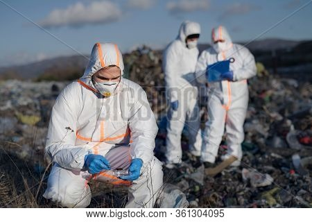 Group Of Activists With Protective Masks On Landfill, Environmental Pollution Concept.
