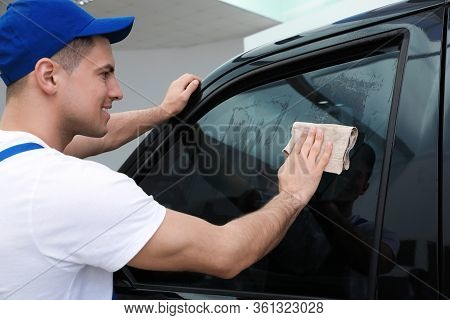 Worker Washing Tinted Car Window In Workshop