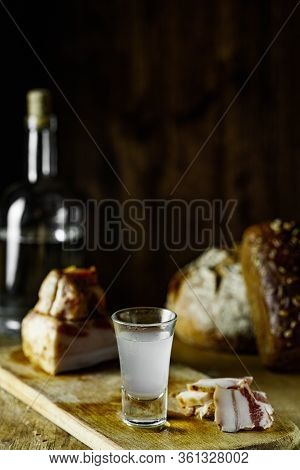 Rye Bread, Lard, Vodka, A Glass Of Vodka On A Cutting Board On A Wooden Table And On A Black Backgro