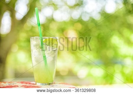 Homemade Fresh Cool Lemonade From Juice With Fresh Lemons And Mint. A Glass Of Lemonade Against A Ba