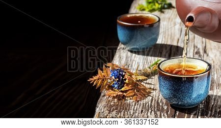 Hot Green Tea Is Poured From The Teapot Into The Blue Bowl, Vintage Wooden Table, Steam Rises Above