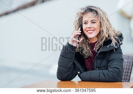 Pretty Female Speaking For Smart Phone Sits In Outdoor Cafeteria