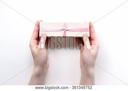 Gift Box With Pink Ribbon In Female Hands On White Background Top View. Christmas, New Year, Valenti