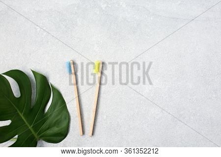 Bamboo Toothbrushes And Green Leafs On Light Stone Table. Zero Waste Concept For Self-care . Plastic