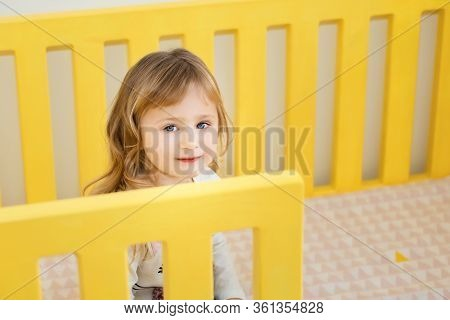 Little Smiling Blonde 3 Years Old Girl Sitting In Yellow Cot In Her Bedroom. Time To Play During Sel