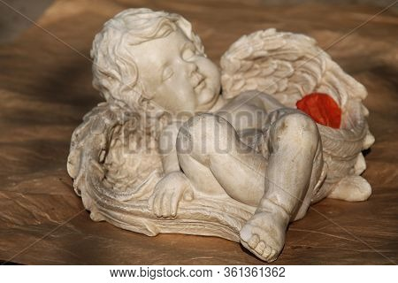 Statuette Of A Little Sleeping Angel Of White Color On A Brown Background