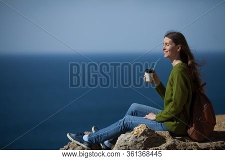 Beautiful Young Woman Traveler With A Backpack Drinking Morning Coffee And Looking At The Sea. Copy