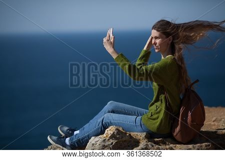A Young Female Traveler Takes A Selfie On Her Smartphone Against The Sea And Smiles, The Wind Blows