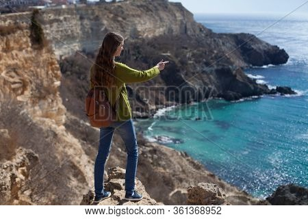 An Attractive Girl Traveler With A Backpack Looks And Points To The Sea Bay. The Concept Of Travel ,