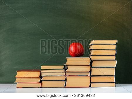 Back To School, Pile Of Books And Red Apple With Empty Green School Board Background, Education Conc