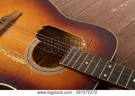 Musical Instrument - Closeup Fragment Broken Classic Acoustic Guitar On A Wooden Background.