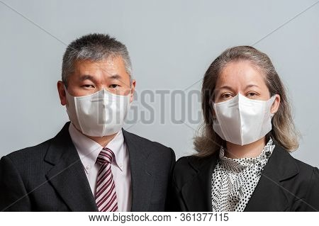 Front View Of Middle Aged Asian Couple In Formal Wear Wearing White Disposable 3d Face Mask For Prot