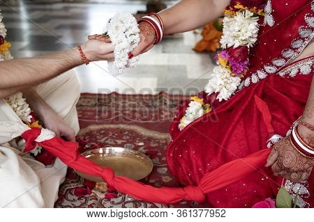 The Bride And Groom Hold Hands Tied With A Garland Of White Flowers. Beautiful Traditional Indian We