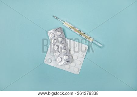 Flatlay With Mercury Thermometer And Pills Isolated On Blue Background.