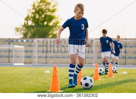 Footballer Running With Ball On Training Pitch. Soccer Practice For Junior Level Team. School Sports