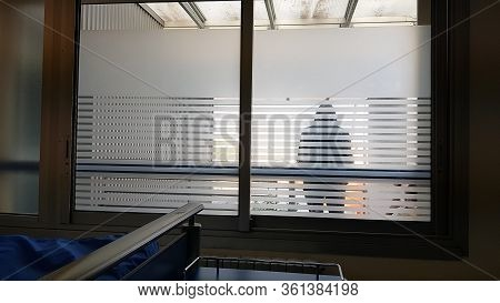 Silhouette Of A Person Seen From The Back Inside The Hospital. Loneliness And Pain In Hospital Due T
