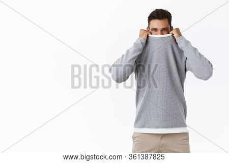 Cheerful And Coquettish Cute Handsome Young Modern Guy Hiding In Sweater Collar, Pull Cloth Up On Fa