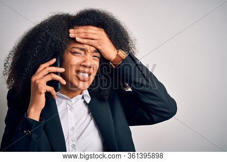 Young african american business woman with afro hair calling using smartphone mobile stressed with hand on head, shocked with shame and surprise face, angry and frustrated. Fear and upset for mistake.