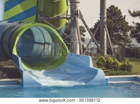 Big Striped Water Slide For Extreme Descents On An Inflatable Circle In The Water Park