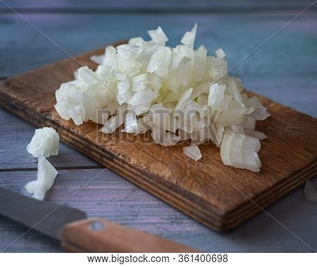 Close-up Chopped Onion In Small Cubes On A Cutting Board On A Rustic Kitchen Table Close-up