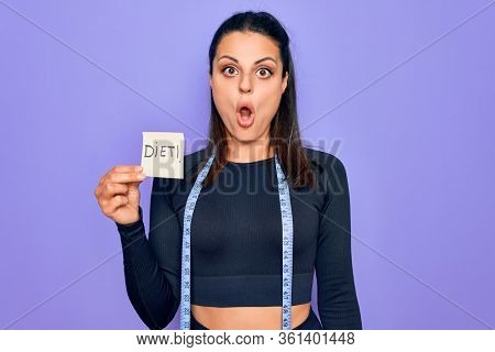 Young beautiful brunette sporty woman using tape measure holding reminde with diet message scared and amazed with open mouth for surprise, disbelief face