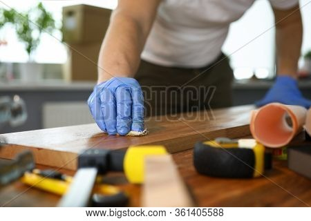 Close-up Of Male Hands In Protective Gloves Grinding Wooden Surface. Equipment And Tools On Working