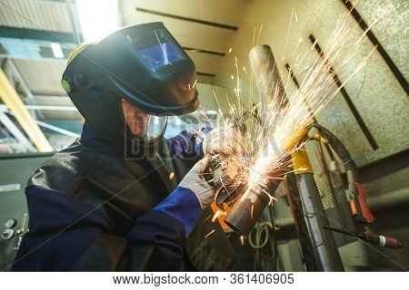 Welding and sanding joints. industrial worker machining weld seam with grinder machine