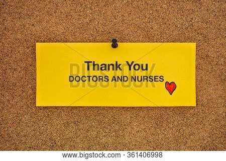 Thank You Doctors And Nurses Written On A Yellow Piece Of Paper That Is On A Bulletin Board. Coronav