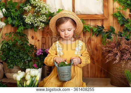 Little Girl In Dress And Straw Hat Sits On Porch Of Wooden House Around Green Houseplants And Flower