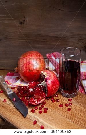 Fresh Red Pomegranate With Vintage Knife And Glass Of Fresh Rudy Juice On A Wooden Background..