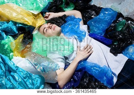 Young Man With Blue Eyes, Lying Down, With Ring In Nose, Surrounded By Plastic Bags, Looking Up. Hor