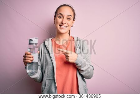 Young beautiful sporty woman doing sport drinking bottle with water to refreshment very happy pointing with hand and finger
