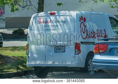 Young Youthful Fast Food Worker Working At Chick-fil-a Drive Through Amidst Cars Tak Take Orders Wit