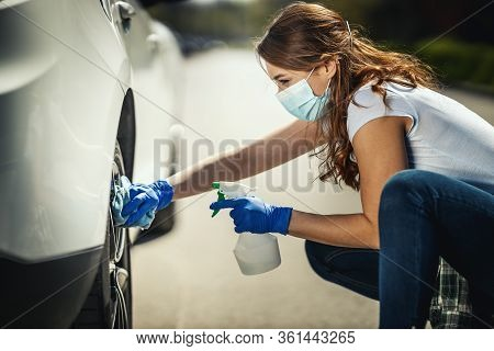 A Young Woman With A Mask On Her Face And Protective Gloves On Her Hands, Wipes Her Car Holding A Cl
