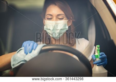A Young Woman With A Mask On Her Face  And Protective Gloves On Her Hands Wipes A Steering Wheel In