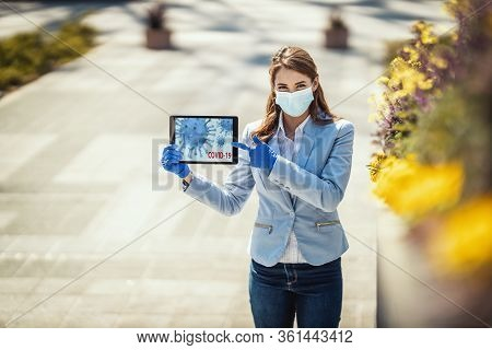 Young Business Woman With Protective Mask On Their Face Is Showing An Animation Of A Corona Virus On