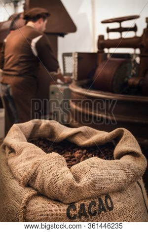 Jute Bag Full Of Cocoa Beans In A Chocolate Maker Workshop, With A Male Chocolatier Working On Conch