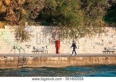 Split,croatia April 2020 Girl Walking A Dog Near The Sea On The Bacvice Beach Of Split. Realistic Sh