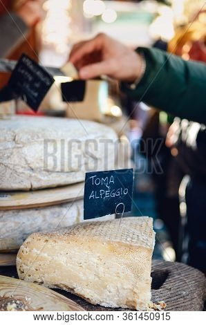 Market Stall With Italian Hard Cheese Sliced And Open, Alp Cheese Label (toma Alpeggio) On Foregroun