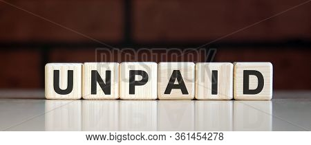 Unpaid - Business Financial Concept On On A Dark Brick Background. Wooden Cubes With Text