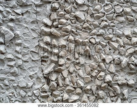 Gray Stucco With Large Pebbles. On The Left, The Pebbles Fell Away And Left Dents In The Cement. Bac